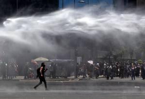 Manifestante caminha enquanto a polícia chilena lança jato de água para dissolver protesto em Santiago Foto: CLAUDIO REYES/AFP/26-11-2019