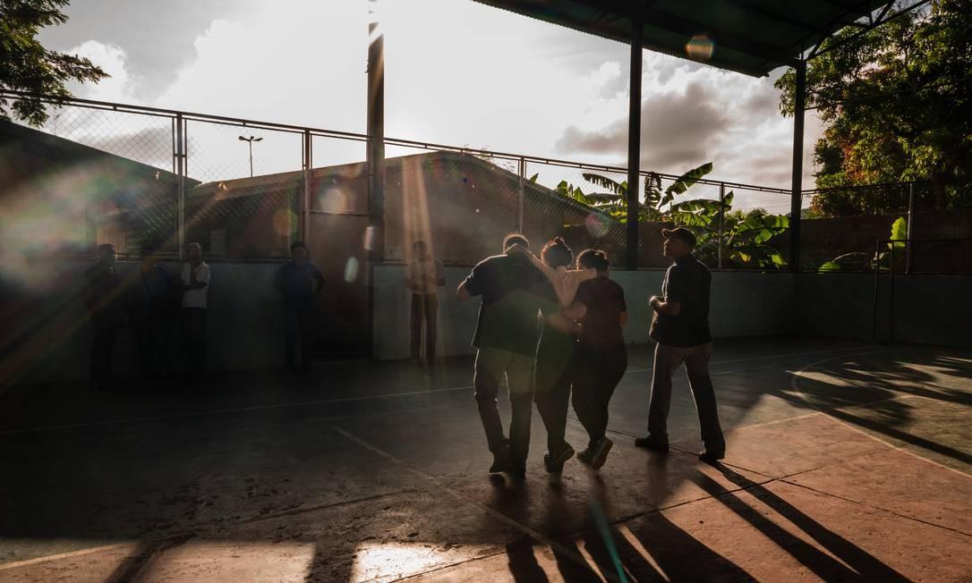 Professores carregam uma estudante que desmaiou na Escola Augusto D'Aubeterre, em Boca de Uchire, Venezuela: muitos alunos chegam para a aula sem ter tomado café ou jantado na noite anterior Foto: Adriana Loureiro Fernandez/The New York Times