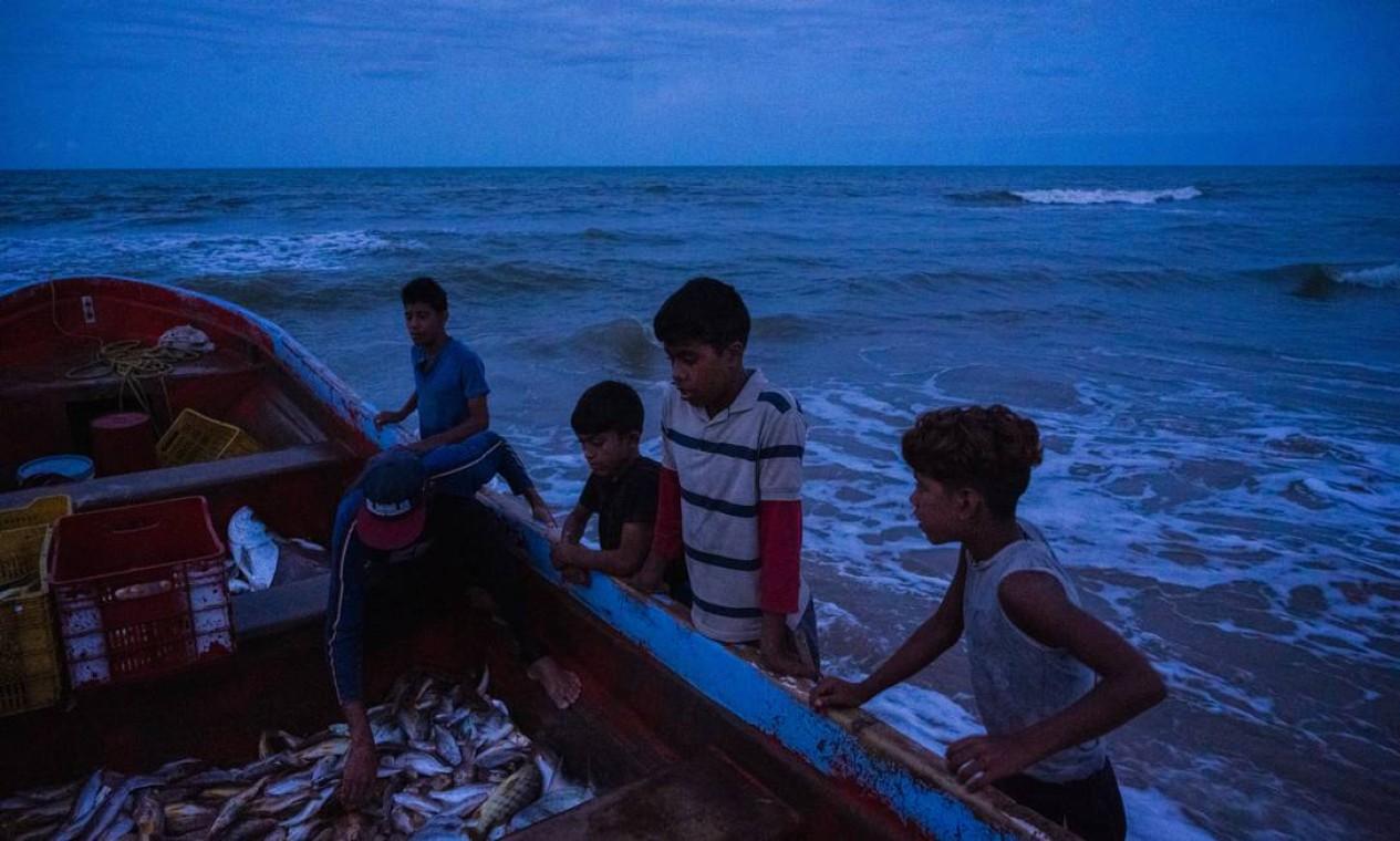 Crianças pedem peixe a um pescador em Boca de Uchire, Venezuela: muitas deixaram a escola para ajudar os pais na pesca ou em plantações Foto: ADRIANA LOUREIRO FERNANDEZ / Adriana Loureiro Fernandez/The New York Times