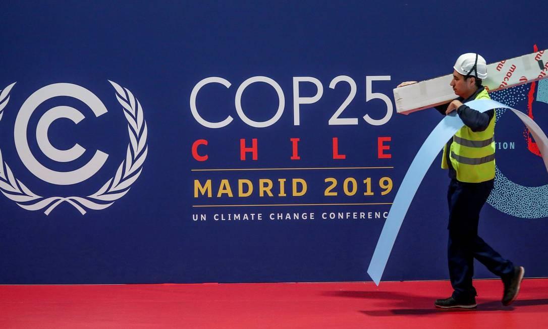 Funcionário passa diante de painel da COP 25, em Madri Foto: SERGIO PEREZ / REUTERS