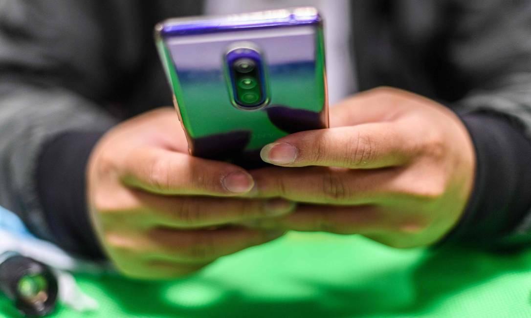 Para registrar cartões SIM com operadoras de telefonia, chineses terão que passar por escaneamento facial para confirmar fotografias da carteira de identidade apresentada Foto: ANTHONY WALLACE / AFP