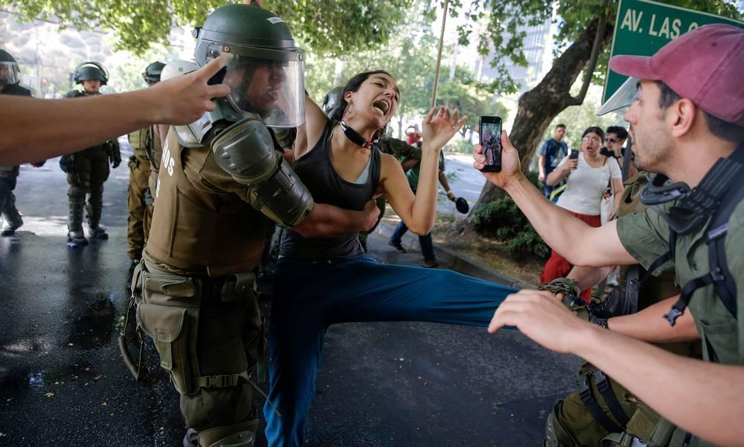"""Manifestante é detida por policiais durante protesto em celebração do """"infeliz aniversário"""" de Piñera, cuja popularidade atingiu o mínimo histórico: 10% Foto: Javier Torres / AFP"""