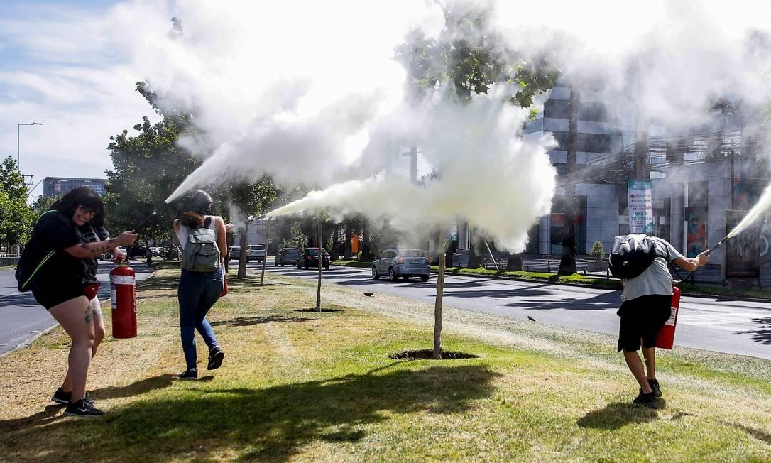 Extintores de incêndio foram usados contra vizinhos em confrontos durante um protesto perto da casa do presidente chileno, Sebastián Pinera, em Santiago, neste domingo Foto: Javier Torres / AFP
