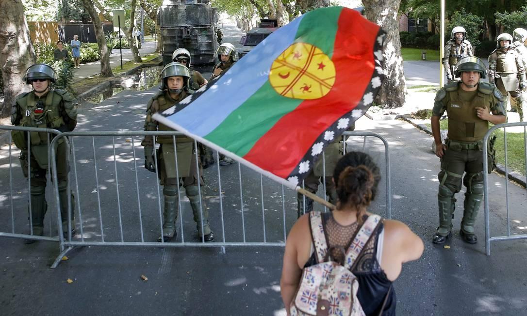 Manifestante agita uma bandeira mapuche em frente ao cerco montado por policiais para isolar a casa do presidente chileno, Sebastián Piñera. Bandeira representa povos nativos do Chile e é usado como símbolo da luta popular Foto: Javier Torres / AFP