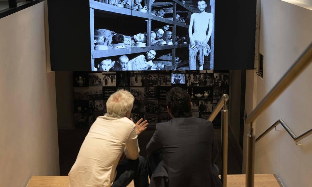 Visitantes assistem a uma tela durante turnê de imprensa no Museu do Holocausto. Recursos tecnológicos, telas sensíveis ao toque, espaços sensoriais e tablets interativos destacam os testemunhos de sobreviventes, fotos e vídeos históricos, enquanto estatísticas dolorosas completam a informação Foto: JUAN MABROMATA / AFP