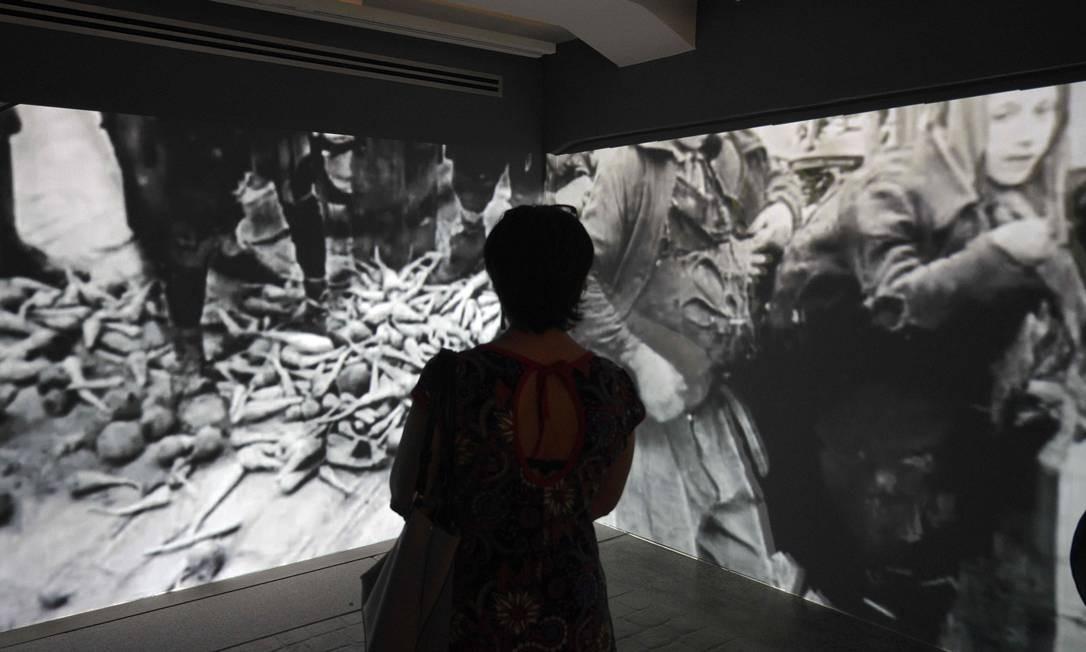 Mulher assiste a uma projeção de filmes nazistas no Museu do Holocausto em Buenos Aires. O museu, que abriga uma exposição permanente sobre o extermínio de seis milhões de judeus nas mãos do nazismo durante a Segunda Guerra Mundial (1939-1945), foi reaberto ao público no domingo (1º de dezembro), após dois anos fechado Foto: JUAN MABROMATA / AFP