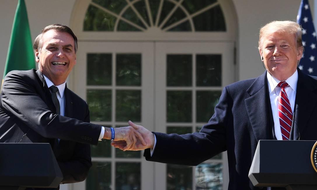 O presidente americano, Donald Trump, aperta a mão do presidente Jair Bolsonaro no jardim da Casa Branca: relações desequilibradas Foto: Jim Watson / AFP/19-3-2019