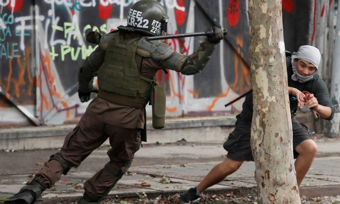 Policial ataca manifestante em Santiago no Chile. Protestos que começaram em 18 de outubro em reação ao reajuste do bilhete de metrô já provocam retração do PIB e rejeição de 82% do presidente Sebastián Piñera Foto: Goran Tomasevic / Reuters