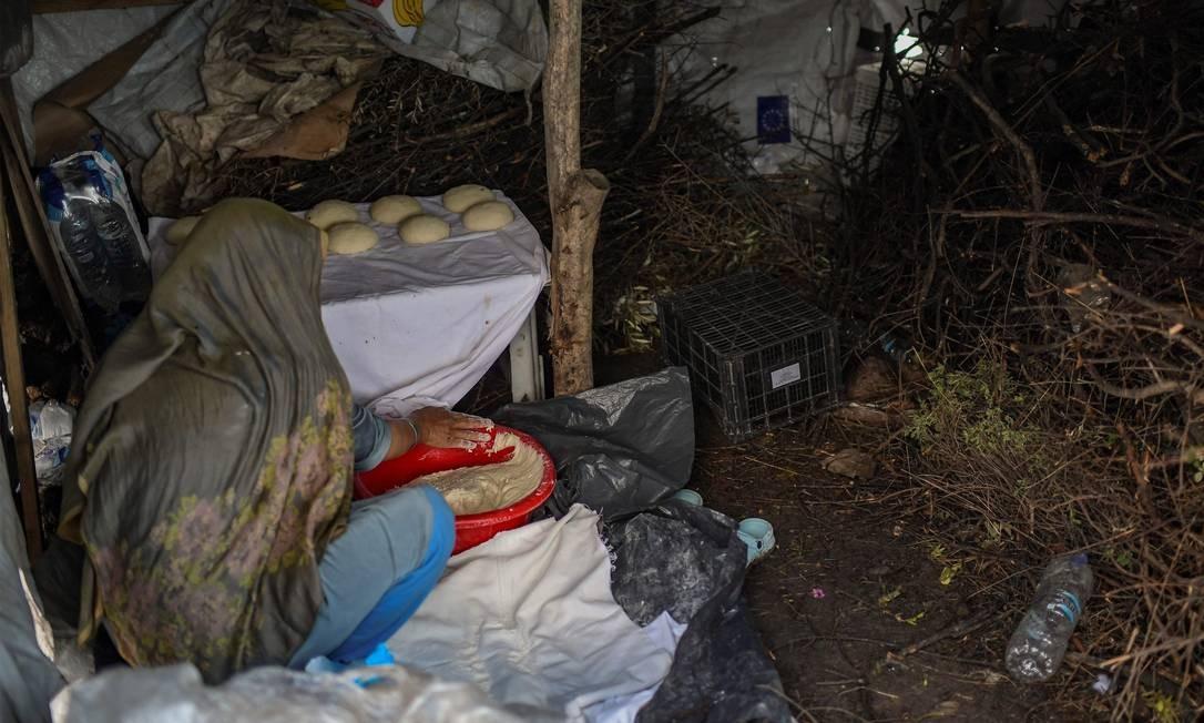 Uma mulher prepara pão dentro de uma barraca no campo improvisado próximo ao campo de refugiados superlotado de Moria Foto: Aris Messinis / AFP