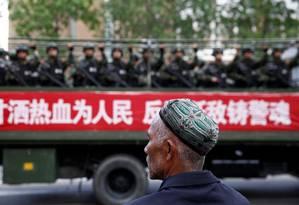 Homem da minoria muçulmana uigur observa caminhão de policiais em Urumqi, na região autônoma de Xinjiang Foto: Reuters/23-05-2014