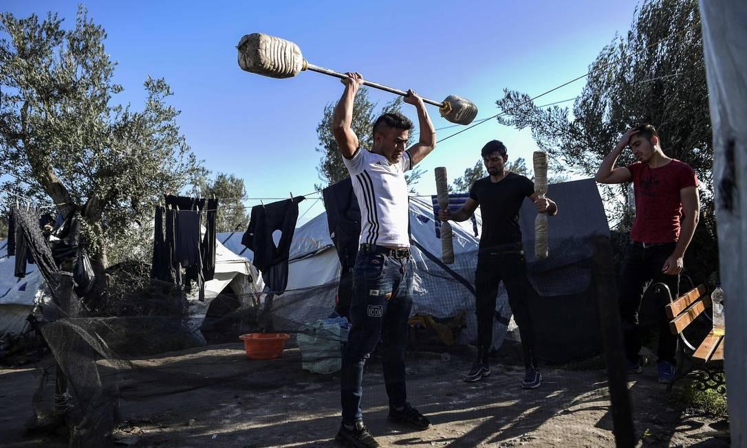 Jovens treinam com halteres improvisados na ilha de Lesbos, localizada à frente da Turquia Foto: Aris Messinis / AFP