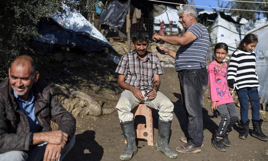 Pessoas refugiadas tentam manter rotina, mesmo em condições precárias Foto: Aris Messinis / AFP
