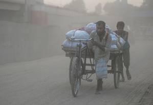 Homens puxam carrinho em Dhaka, Bangladesh: poluição atmosférica preocupa OMS Foto: MUNIR UZ ZAMAN/AFP/25-11-2019