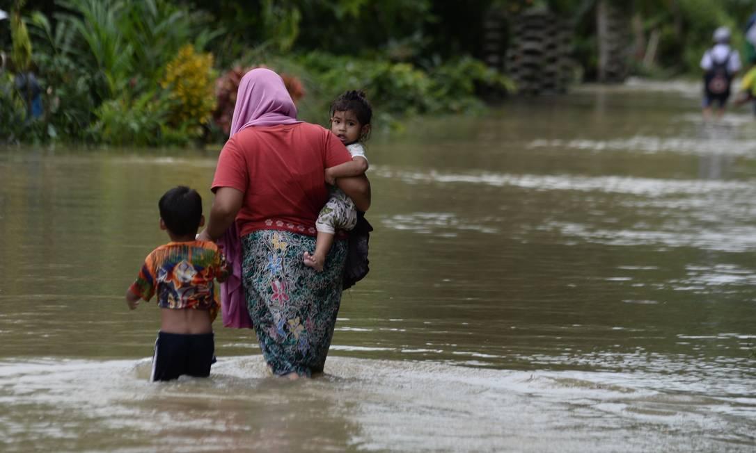 Mulher caminha com dois filhos nas águas da enchente após fortes chuvas na província de Narathiwat, no Sul da Tailândia, em 3 de dezembro de 2019 Foto: MADAREE TOHLALA/AFP