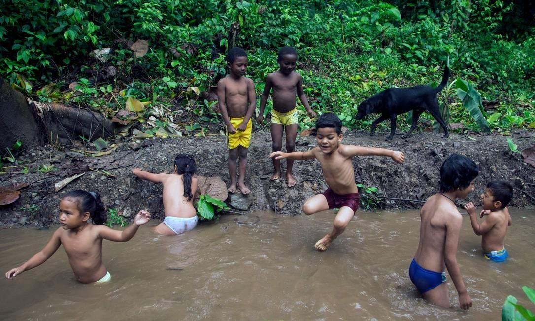 Alunos da Escola Florestal Pambilino brincam em uma piscina feita com lama e água de um rio em San Jose de Mashpi. As crianças aprendem a importância da natureza em uma escola florestal localizada na biosfera reserva no Equador. A área é um território único, no qual o desenvolvimento social e econômico das comunidades tende a uma relação harmoniosa com o ambiente natural Foto: Cristina Vega Rhor / AFP
