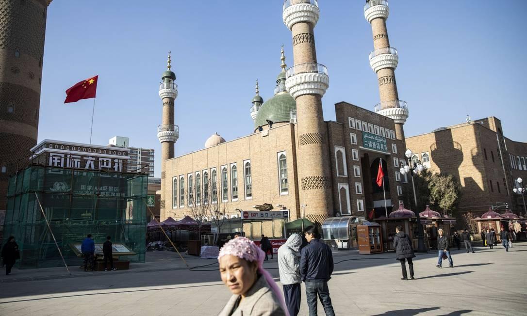 Turistas e agentes de segurança praça do principal mercado de Urumqi, capital da província chinesa de Xinjiang, em novembro do ano passado: políticas de repressão do governo central da China à minoria muçulmana uigur na região são alvo de denúncias de violações dos direitos humanos Foto: Bloomberg / Qilai Shen/Bloomberg/06-11-2018