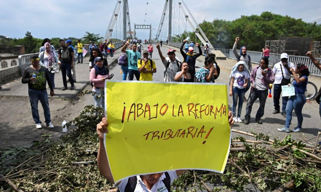 """Um manifestante antigoverno segura uma placa com a inscrição """"Abaixo a reforma tributária"""" ao bloquear uma ponte em Cali; bloqueios rodoviários afetaram os sistemas de transporte Foto: LUIS ROBAYO / AFP"""