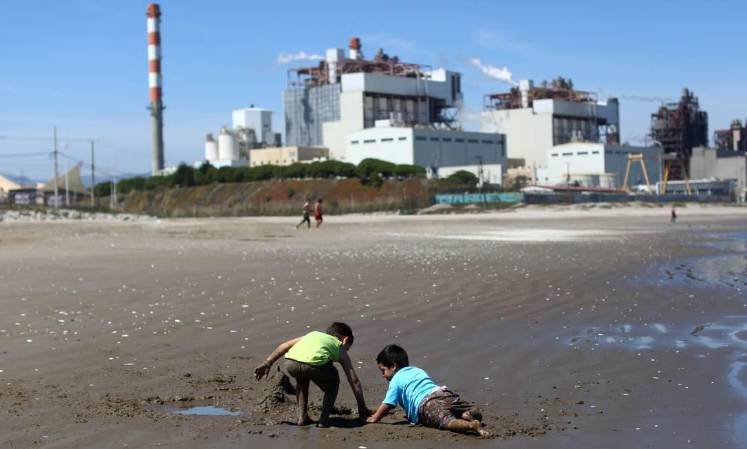 """Crianças brincam na areia na praia de Las Ventanas, perto da usina termelétrica AES Gener, em Valparaiso, no Chile. Quintero e Puchuncaví, localidades consideradas o """"Chernobyl chileno"""", sofrem com poluição do ar, mar e terra há mais de cinco décadas, o que também intoxica sua população Foto: PABLO VERA / AFP"""