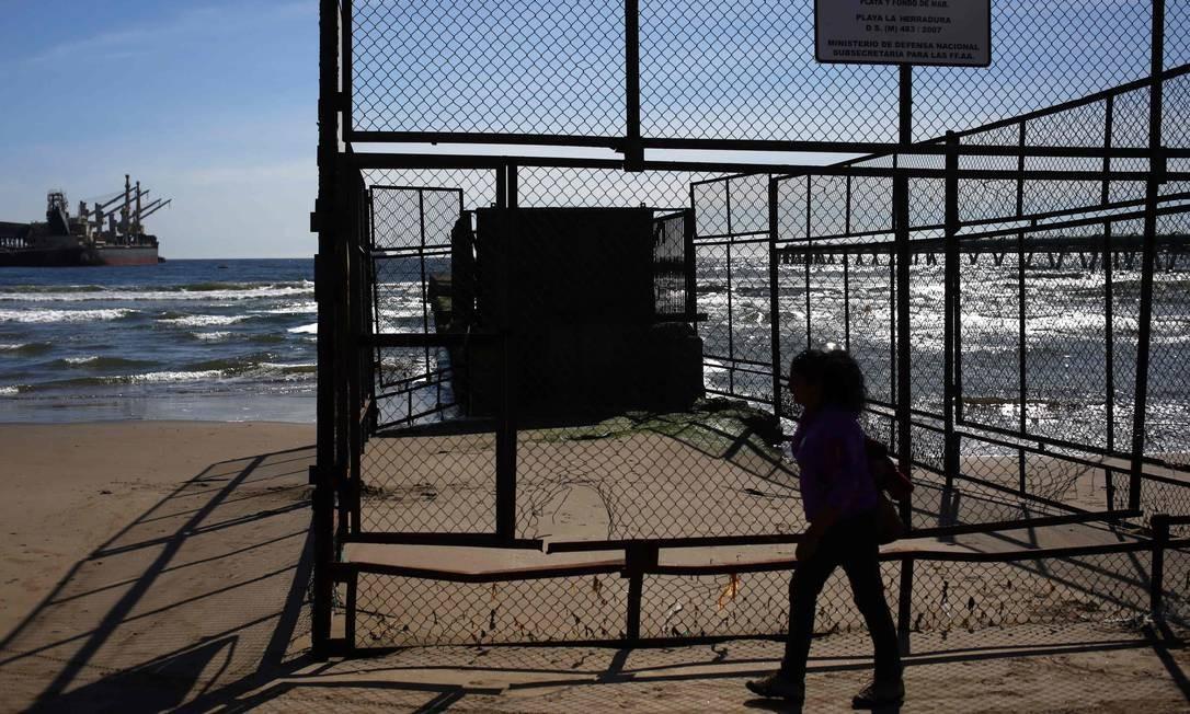 Uma mulher passa por dutos em Puerto Ventanas. Polo industrial abriga quatro termelétricas a carvão e refinarias de petróleo e cobre Foto: PABLO VERA / AFP