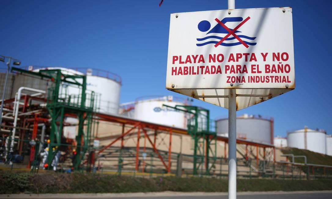 """Placa alerta a população com a inscrição """"Praia não adequada e não é habilitada para banho, zona industrial"""" perto da fábrica química de Oxiquim, cujo tubo vai para a praia de Las Ventanas Foto: PABLO VERA / AFP"""