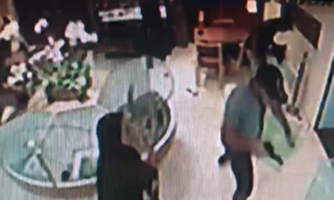 Assaltante armado (de boné) estava entre os quatro que invadiram a loja Foto: Reprodução
