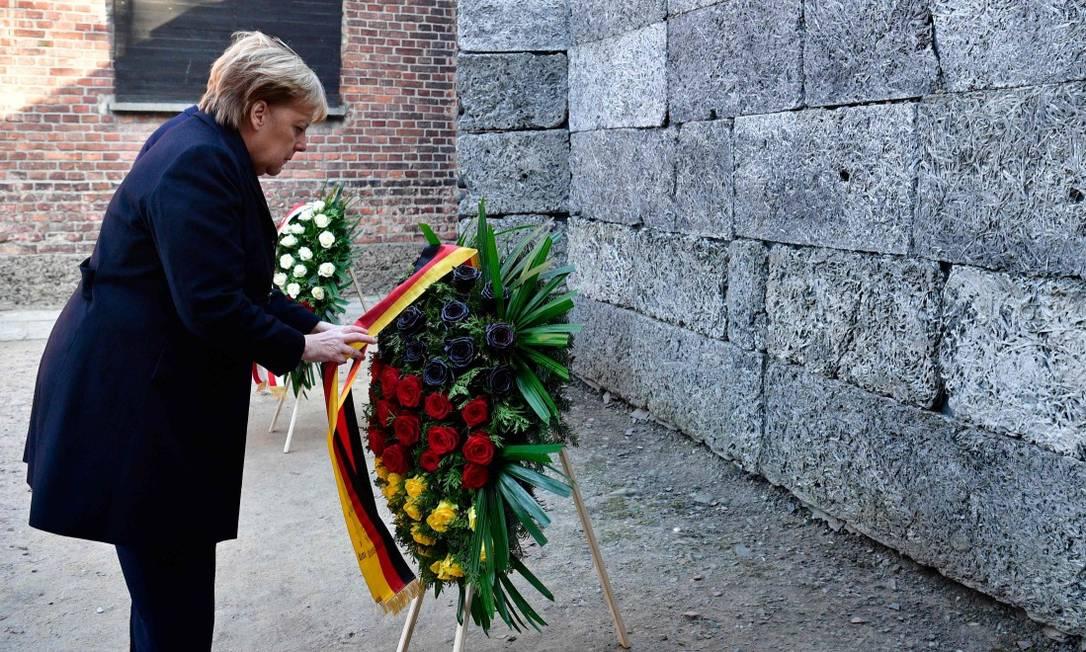 Merkel coloca uma coroa de flores no Muro da Morte, durante sua visita a Auschwitz Foto: JOHN MACDOUGALL / AFP