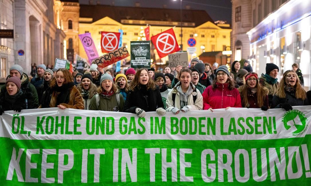 """Estudantes participam de marcha pelo clima em Viena: """"Petróleo, carvão, mantenha-o no chão"""", diz a faixa exbida pelos manifestantes contra a reunião da Organização dos Países Exportadores de Petróleo (OPEP) Foto: JOE KLAMAR / AFP"""