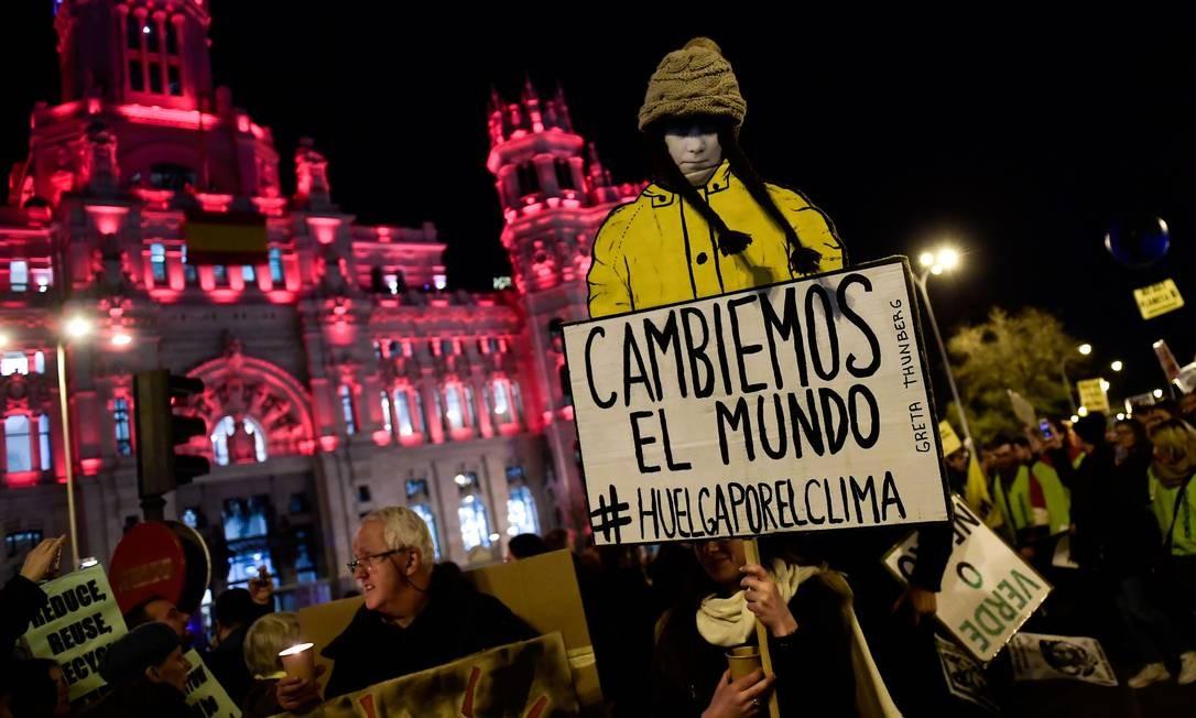 """Manifestantes exibem um cartaz que diz """"vamos mudar o mundo"""", durante a marcha climática na capital da Espanha. Protesto reuniu milhares de pessoas sob o lema """"o mundo despertou diante da emergência climática"""" Foto: CRISTINA QUICLER / AFP"""