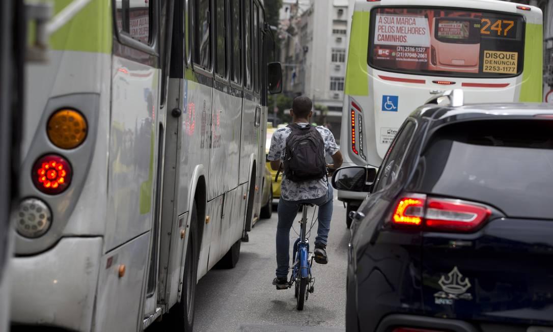 Bicicleta espremida entre ônibus e carro mostra a difícil convivência no trânsito do Rio de Janeiro Foto: Márcia Foletto /