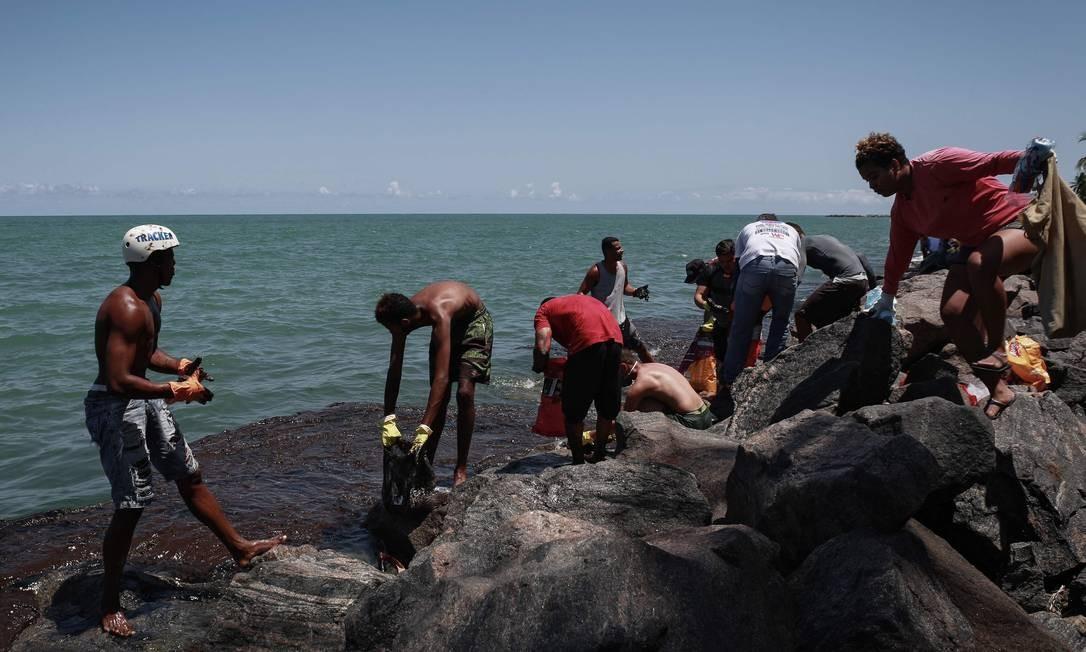 Voluntários coletam óleo em praia de Pernambuco Foto: LEO MALAFAIA/AFP/23-10-2019