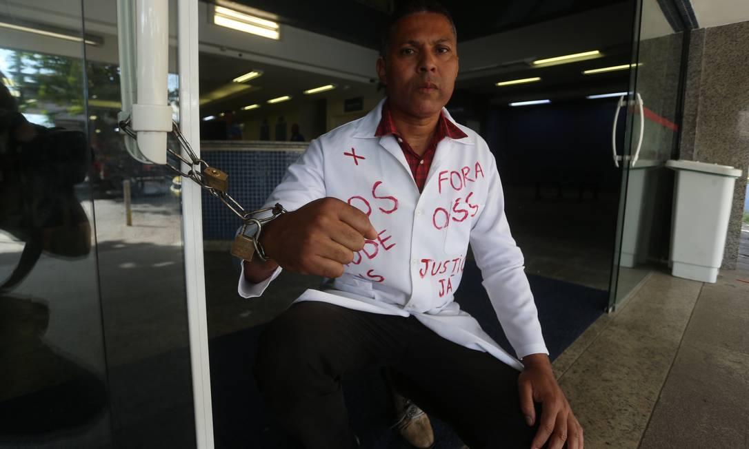 André Luiz Prazeres, ex-técnico de enfermagem do Hospital Albert Schweitzer, se acorrenta à porta da unidade Foto: Fabiano Rocha / Agência O Globo