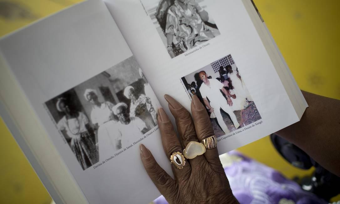 Mãe Meninazinha mostra livro com fotos de antepassados ligados às religiões de matriz africana Foto: Márcia Foletto / Agência O Globo