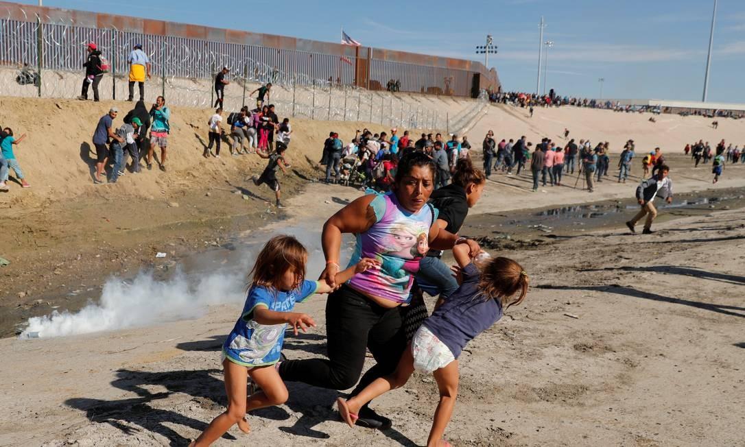 Família tenta escapar das bombas de gás jogadas pelas patrulhas de fronteira perto de Tijuana. Em novembro, 42 mil pessoas foram impedidas de entrar nos EUA pela fronteira com o México Foto: KIM KYUNG-HOON / Reuters