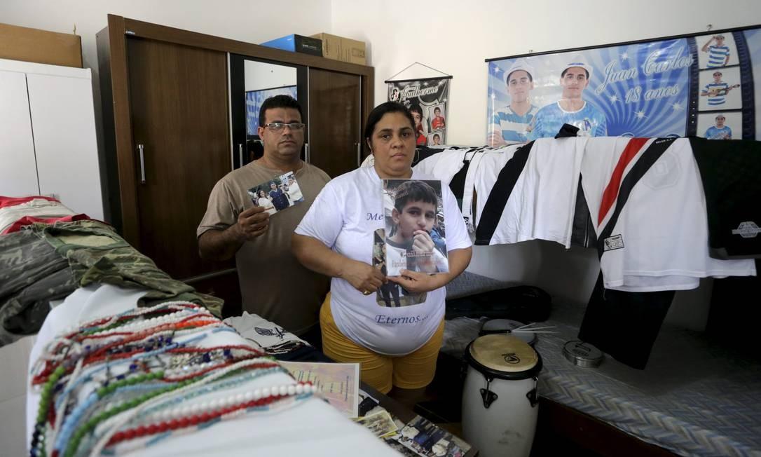 Ana Paula Souza e Carlos Souza com itens que pertenciam aos seus filhos Juan e Guilherme Foto: Domingos Peixoto / Agência O Globo
