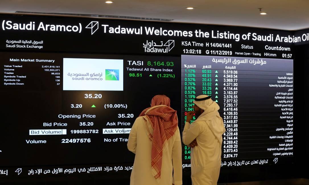Investidores monitoram no telão informações sobre as ações da Aramco, após sua estreia na Bolsa de Riad, na Arábia Saudita Foto: Reuters