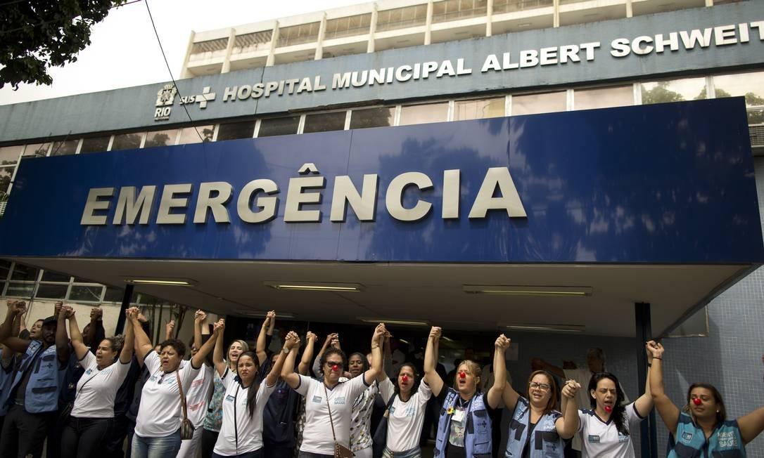 Com nariz de palhaço, funcionários com salários atrasados protestam na porta do Hospital Albert Schweitzer Foto: Márcia Foletto / Agência O Globo