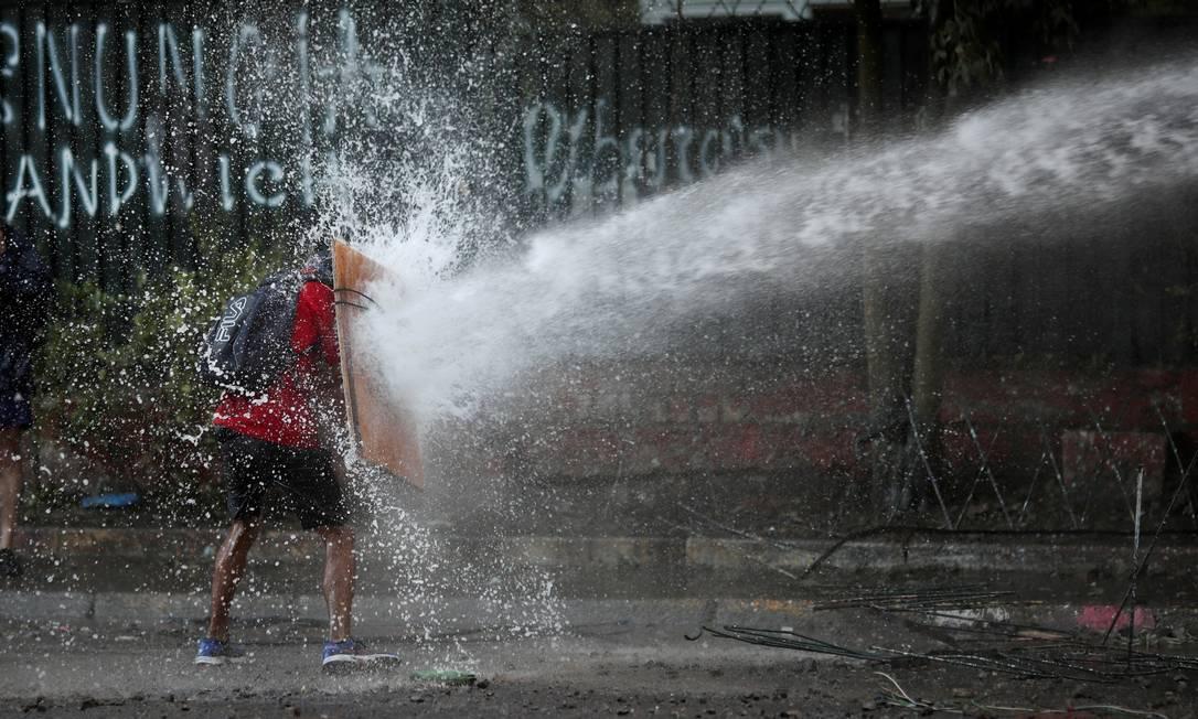 Manifestante usa pedaço de madeira para enfrentar canhão de água durante protesto em Santiago. ONU recomenda que forças de segurança do país adotem abordagem menos violenta nas ruas Foto: RICARDO MORAES / REUTERS
