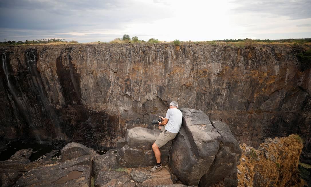 Visitante fotografa as quedas d'água das Victoria Falls, na fronteira do Zimbábue, transformada num abismo seco, em 4 de dezembro Foto: MIKE HUTCHINGS / REUTERS