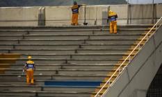 Operários trabalham na arquibancada, que ganha reparos e nova pintura: obras iniciadas em novembro não atacaram os problemas estruturais mais graves da Passarela, apontados em vistorias do Corpo de Bombeiros Foto: Gabriel Monteiro / Agência O Globo