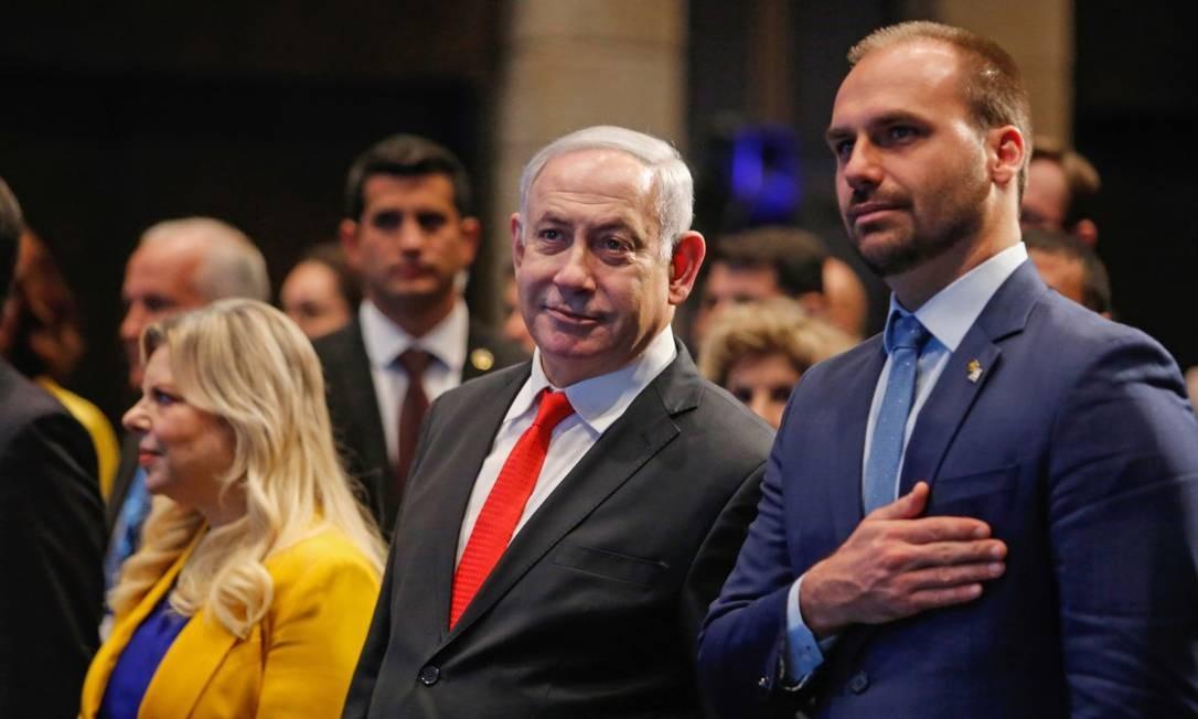 O primeiro-ministro de Israel, Benjamin Netanyahu, entre o deputado federal Eduardo Bolsonaro e sua mulher Sara, durante a cerimônia da inauguração do escritório de negócios do Brasil em Jerusalém Foto: GIL COHEN-MAGEN / AFP