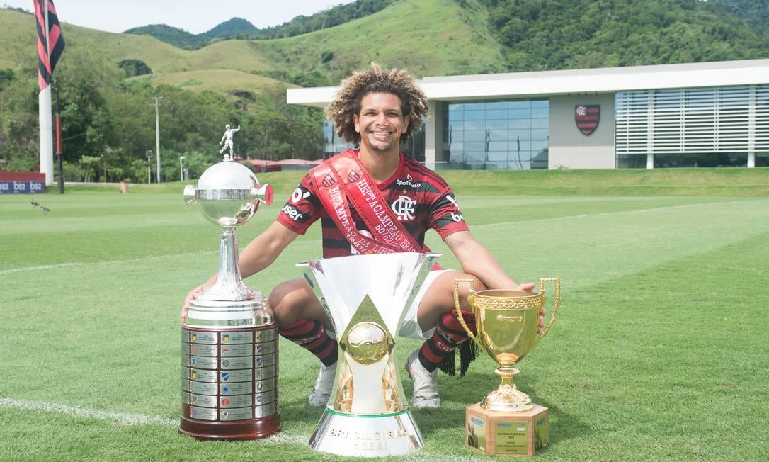 O volante Willian Arão com os troféus de campeão da Libertadores, do Brasileiro e do Estadual Foto: Alexandre Vidal / Flamengo