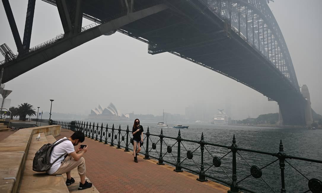 Turistas usam máscaras na Ponte Harbour, em Sydney, para se proteger na fumaça tóxica que tomou conta da cidade e levou mais de 20 mil pessoas aos hospitais Foto: PETER PARKS / AFP