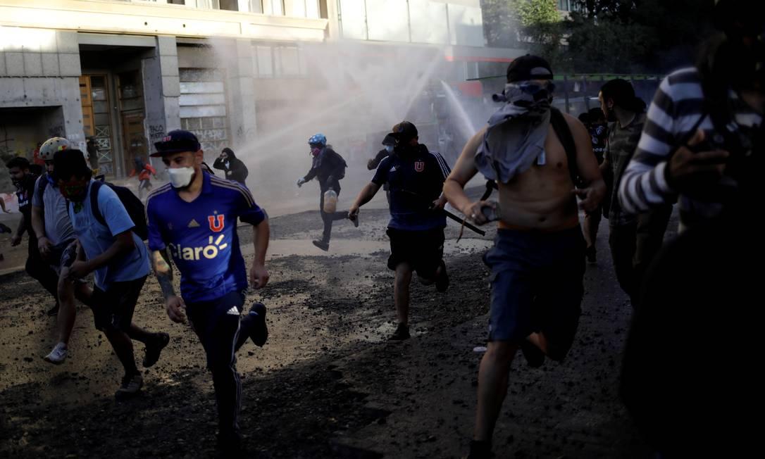 Manifestantes fogem enquanto polícia de choque dispara canhão de água durante protesto contra o governo, em Santiago Foto: ANDRES MARTINEZ CASARES / REUTERS