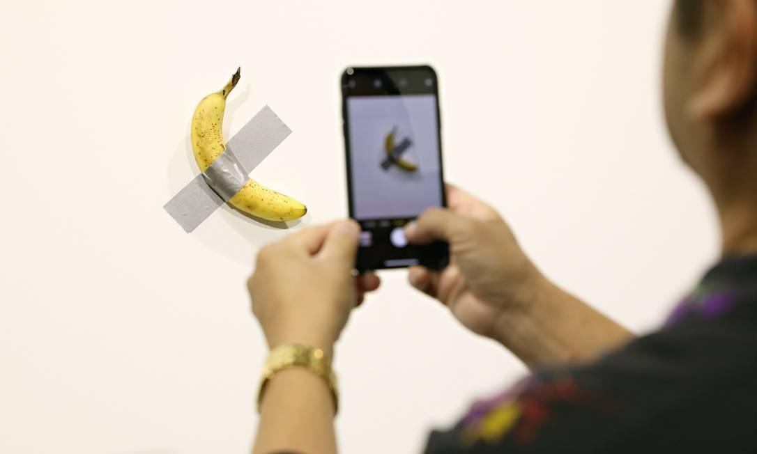 "Visitante fotografa ""Comediante"", obra do italiano Maurizio Cattelan exposta na Art Miami Basel Foto: CINDY ORD / AFP"