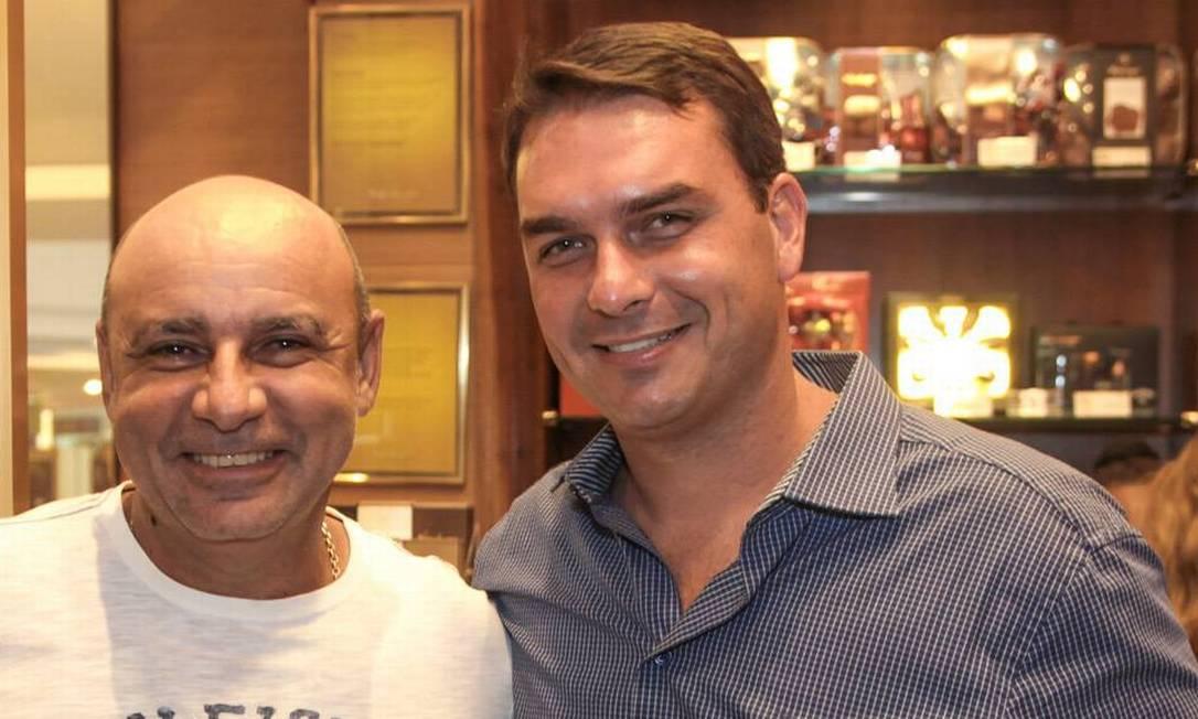 Flávio Bolsonaro, à direita, posa com Fabrício Queiroz na inauguração de sua loja Foto: Reprodução