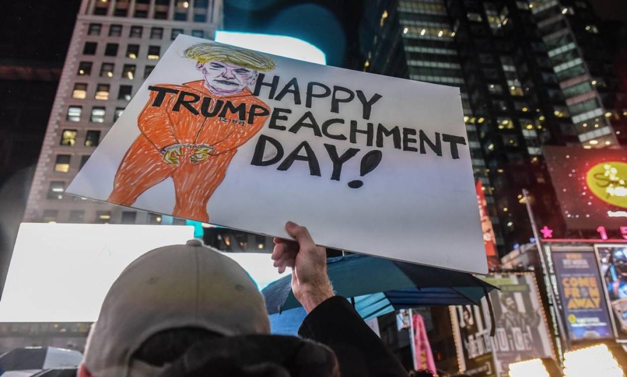 Manifestante exibe cartaz com trocadilho para desejar a saída de Trump Foto: Stephanie Keith / Getty Images / AFP