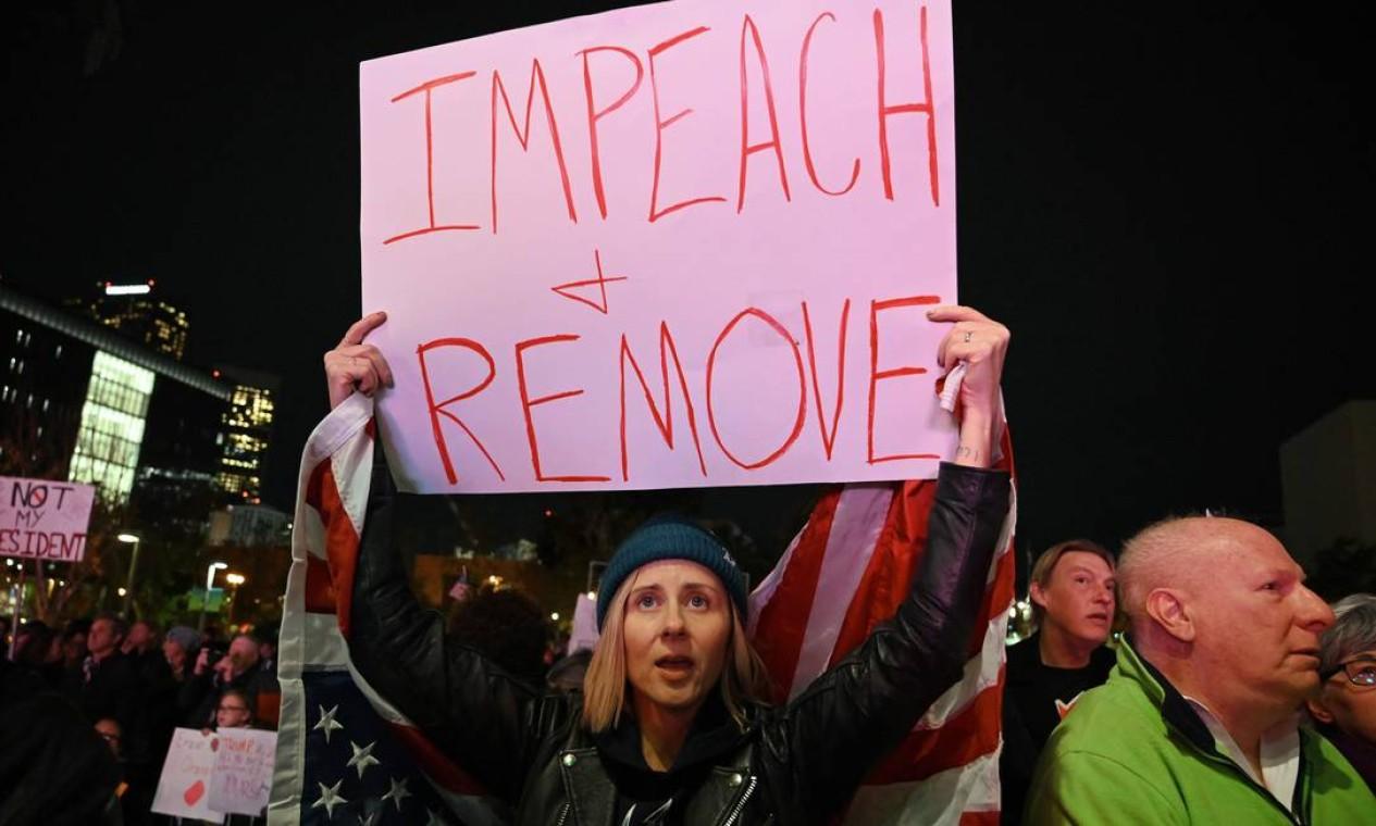 Manifestantes seguram cartazes pedindo o impeachment do presidente dos EUA, Donald Trump, do lado de fora do prédio da prefeitura de Los Angeles Foto: Robyn Beck / AFP