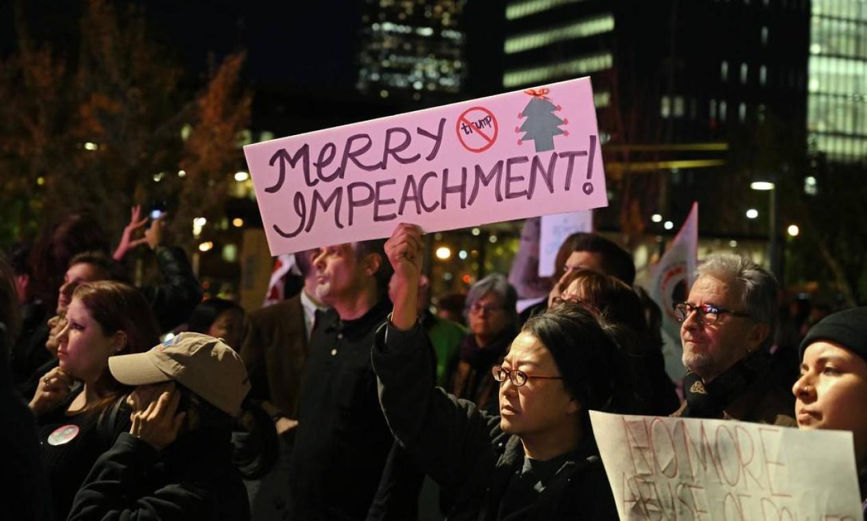 Manifestantes seguram cartazes pedindo o impeachment do presidente dos EUA, Donald Trump, do lado de fora do prédio da prefeitura de Los Angeles, em Los Angeles Foto: Robyn Beck / AFP