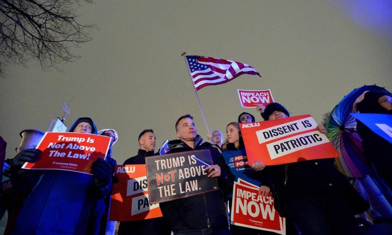 Mais de mil pessoas se reuniram em Boston sob chuva e neve, para pedir o impeachment do presidente Donald Trump na noite de terça Foto: Joseph Prezioso / AFP