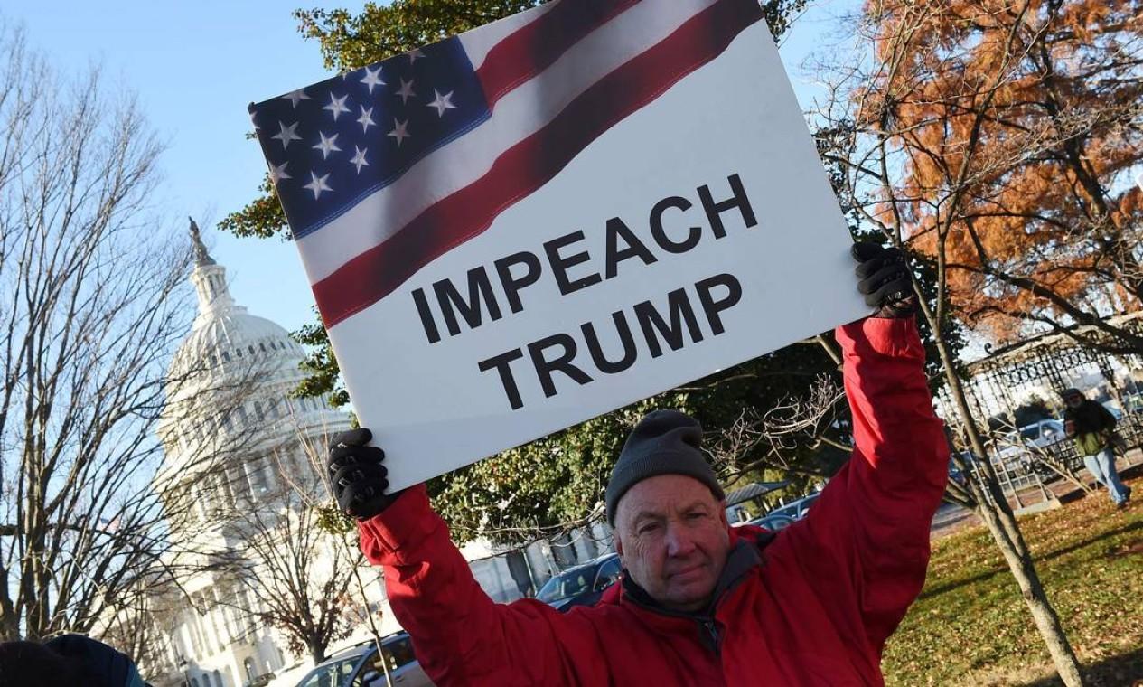 Pessoas se manifestam em apoio ao impeachment do presidente dos EUA, Donald Trump, em frente ao Capitólio dos EUA, enquanto a Câmara se prepara para uma votação histórica nesta quarta-feira Foto: Olivier Douliery / AFP